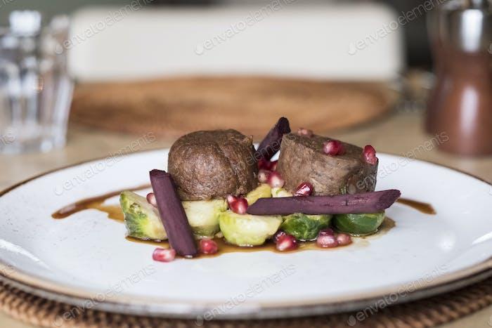 Nahaufnahme von Teller mit Lebensmitteln, Rindfleisch mit Rosenkohl und Rote Bete und eine Beilage von Granatapfel.