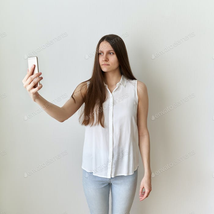 Calm, emotionless woman takes selfie on cell phone. Serious, unflappable female