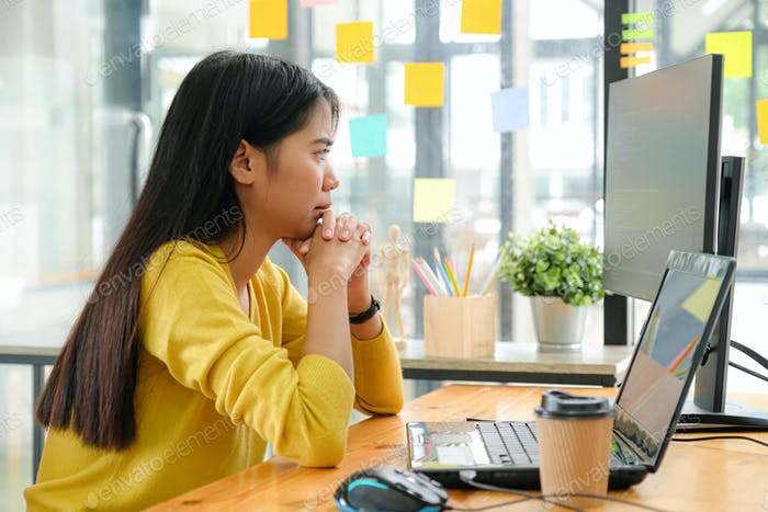 Asian female programmer sitting with hand on her chin,She stared at computer screen and pondered.