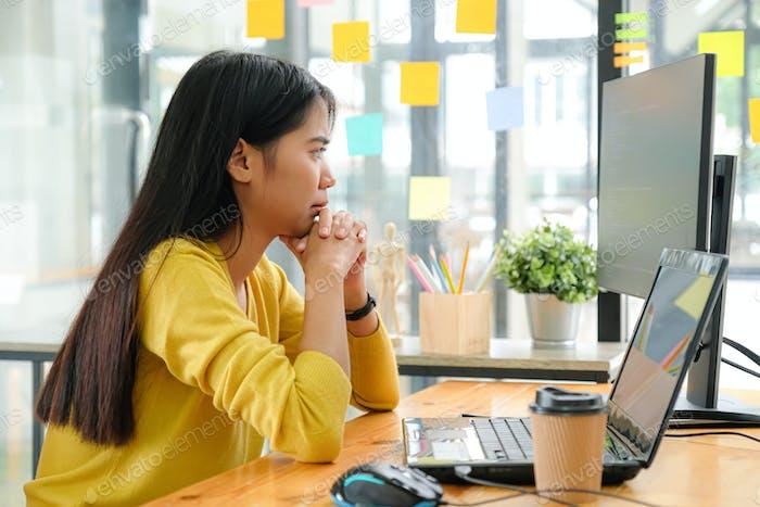Programador Mujer asiático sentado con la Mano en la barbilla, Ella miró a la Completa del Ordenador y reflexionó.