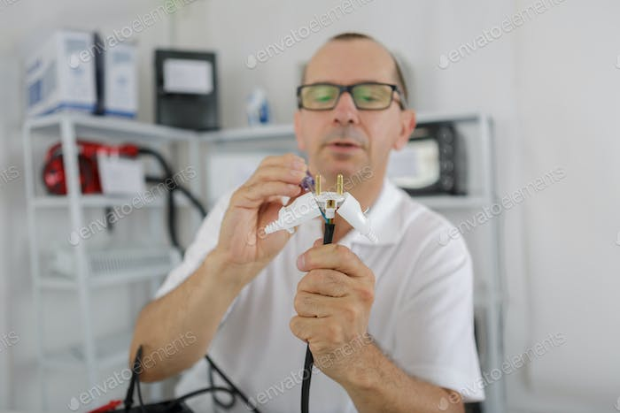 middle-age man fixing a metal instrument