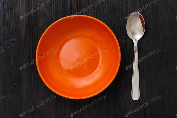orange Schüssel und Löffel auf dunkelbraunem Tisch