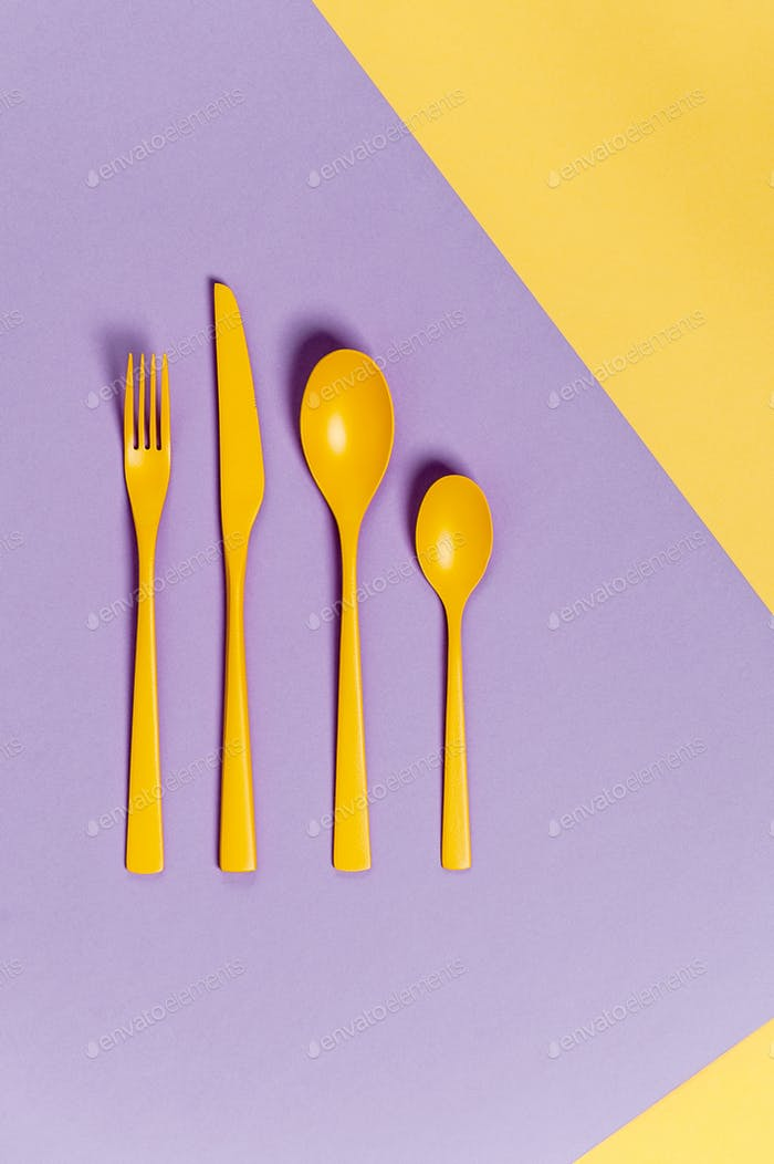 Yellow cutlery on a pastel yellow-lilac background. Colors in th