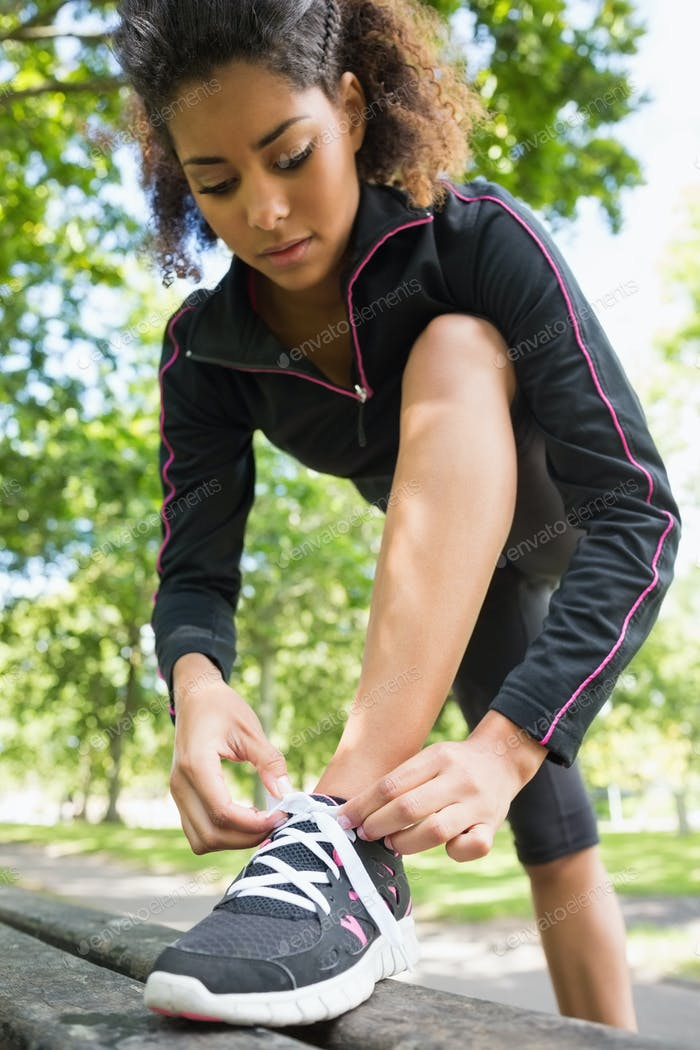 Low angle view of a sporty young woman wearing shoes in the park