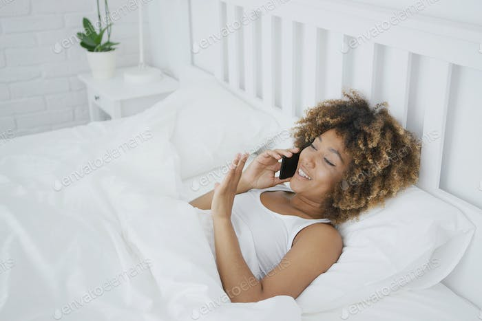Content woman talking on phone in bed