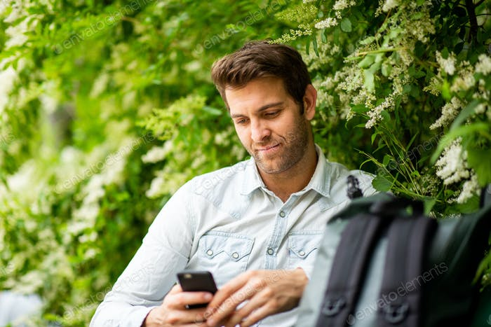 Close up man sitting in park looking at mobile phone