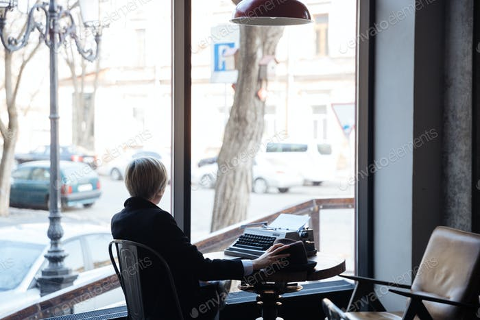 Blonde girl sitting backwards in a cafe
