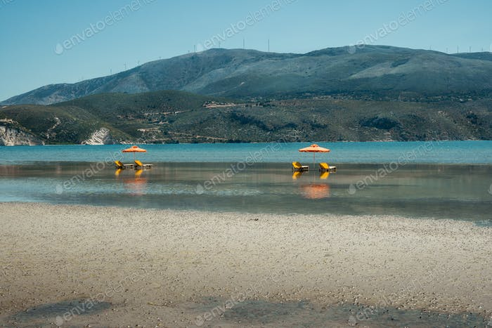 Sunlougers below umbrellas in the shallow water of turquoise bay. Opposite mountainous island with