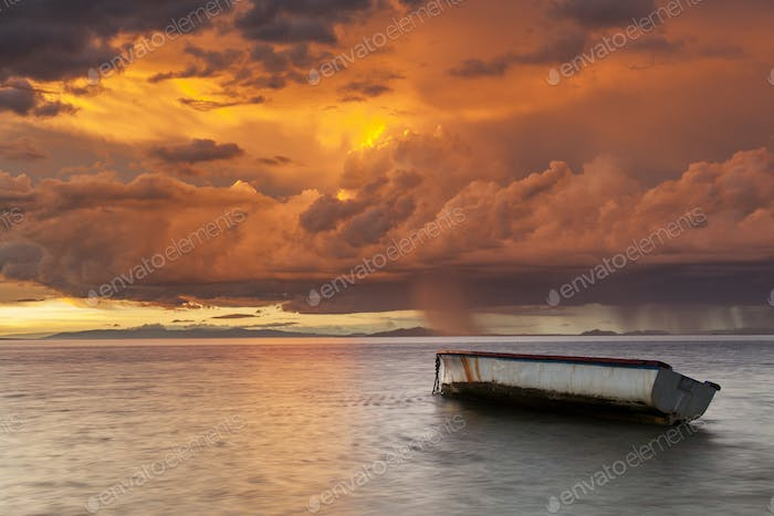 Fishing boat on the background of a dramatic sunset. Mauritius.