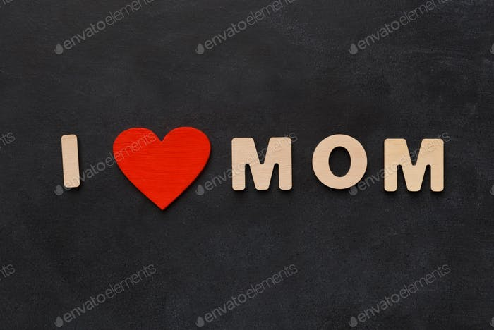 Love mom phrase written on black with wooden letters