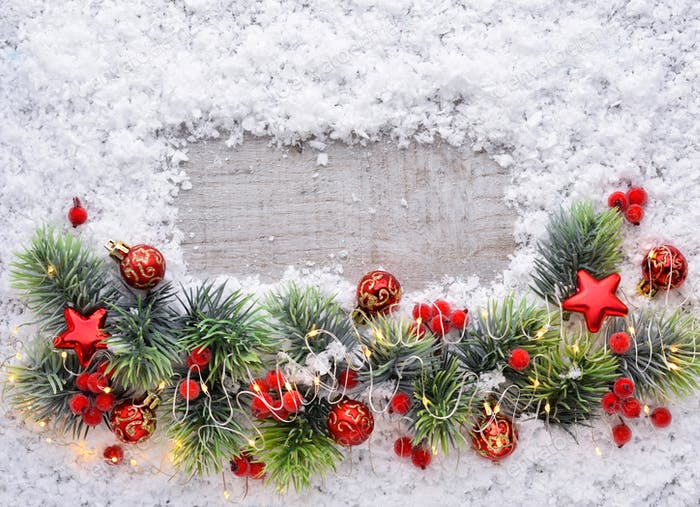 Christmas decorations and spruce branches on snow-covered a wood