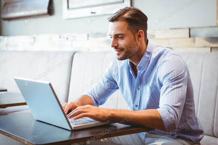 Smiling businessman using his laptop at the cafe