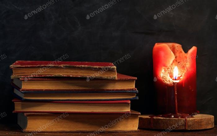 Vintage Bücher und eine Kerze auf einem dunklen Hintergrund