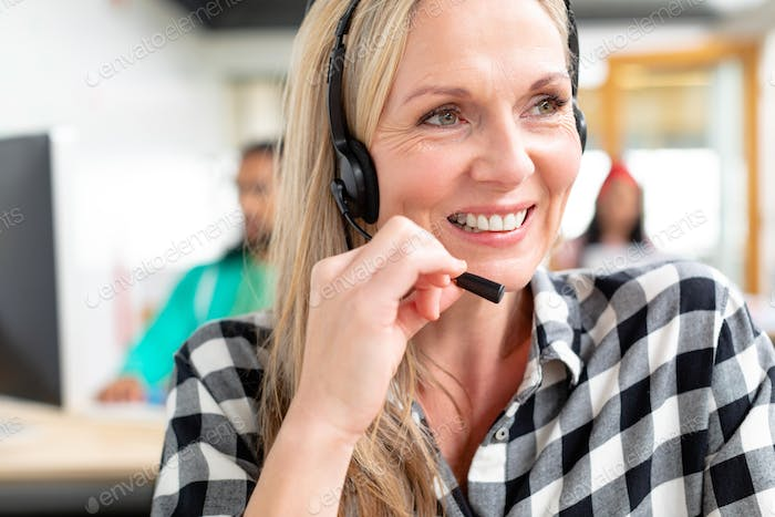 Caucasian female customer service executive looking away while talking on headset