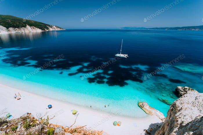 Azure water of Fteri beach, Cephalonia Kefalonia, Greece. White catamaran yacht in clear blue sea