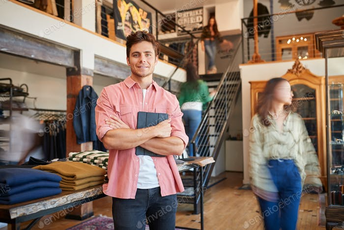 Portrait Of Male Owner Of Fashion Store With Digital Tablet In Busy Clothing Store With Customers