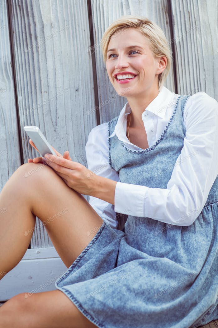Pretty blonde texting with her mobile phone on wooden background