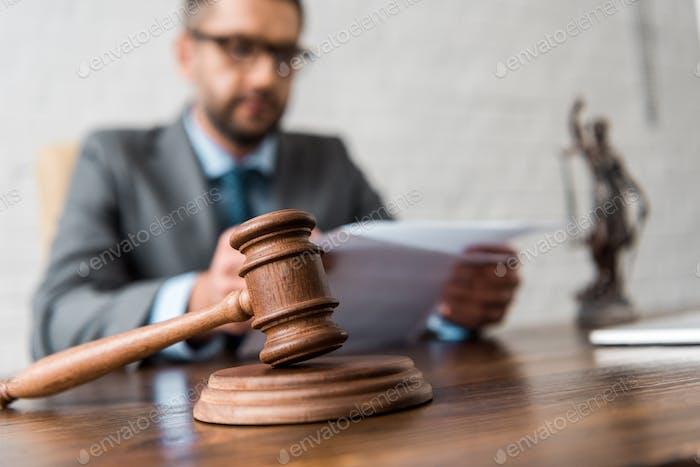 vista de cerca del martillo de madera y juez que trabaja con papeles detrás