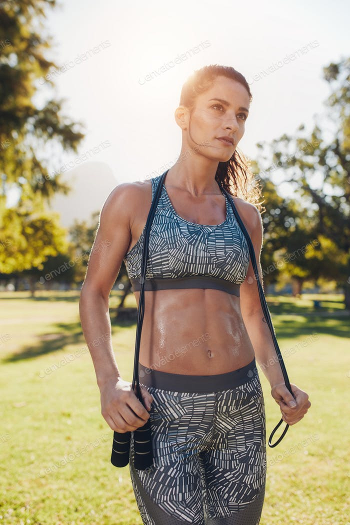 Strong young woman with jump rope