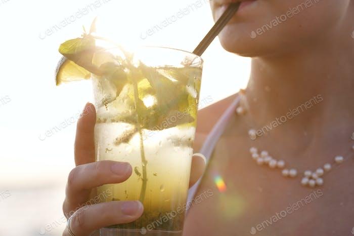 Woman enjoying a tropical mojito cocktail