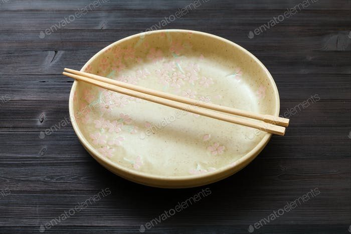 yellow plate with chopsticks on dark brown