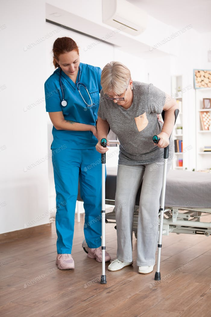 Old woman in nursing home walking with crutches