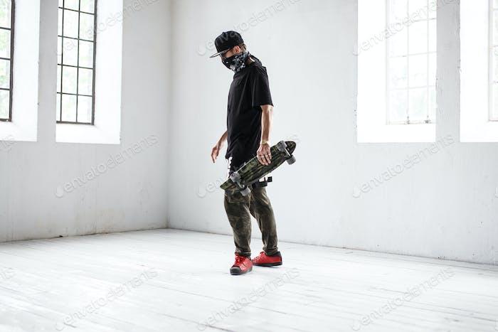 Gangsta Skater in Maske mit Skateboard.