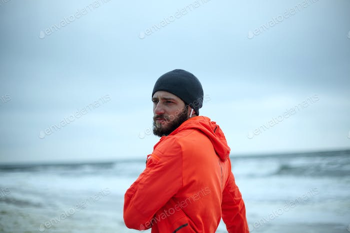 bearded man in warm athletic wear doing warm-up exercises before morning workout