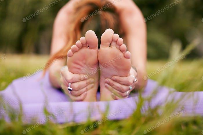 Weibliche Praxis paschimottanasana Yoga auf Gras