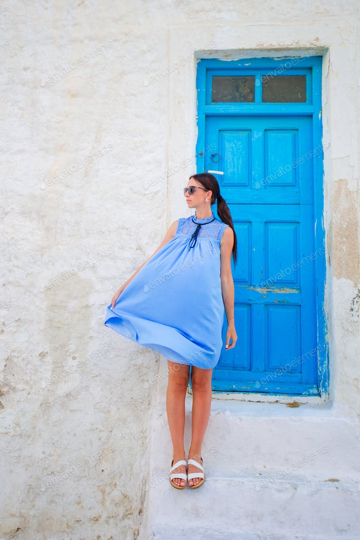 Happy woman on deserted streets of greek village. Young beautiful woman on vacation exploring