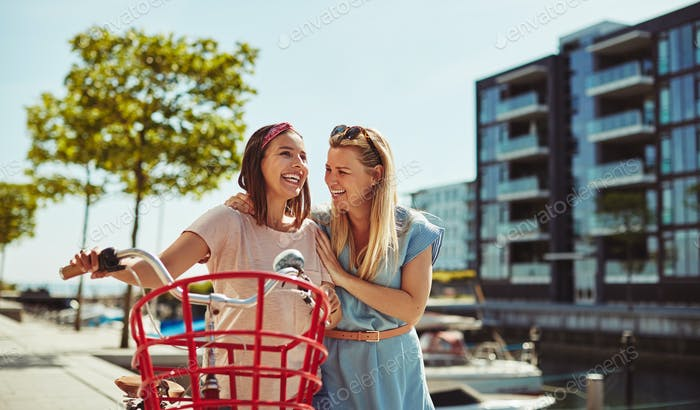 Girlfriends laughing together while walking with a bike in summer