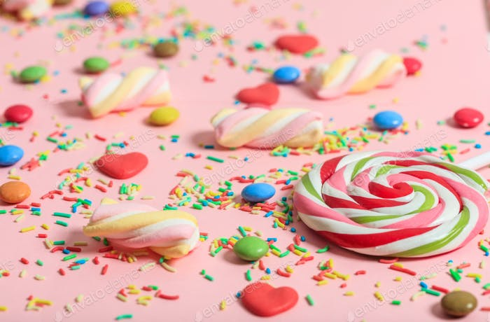 Colorful candies on pink background