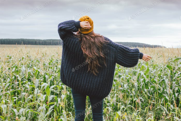Long hair asian girl in yellow hat and knitted sweater from behind in autumn corn field