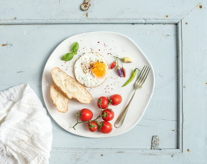 Breakfast set. Fried egg, bread slices, cherry tomatoes, hot peppers and herbs