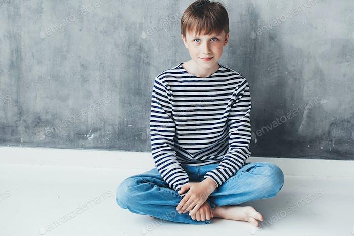 Cute boy happy beautiful child closeup portrait stripes sitting near grey background wall