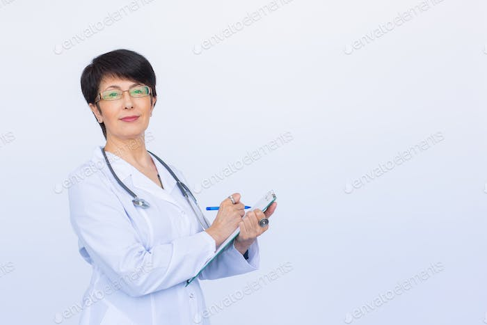 Portrait Of Female Doctor Writing On Clipboard Over a white background with copy space