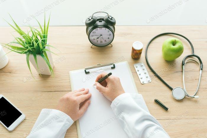 Ärztin Schreiben von Notizen auf Klemmbrett Papier während der medizinischen Ex
