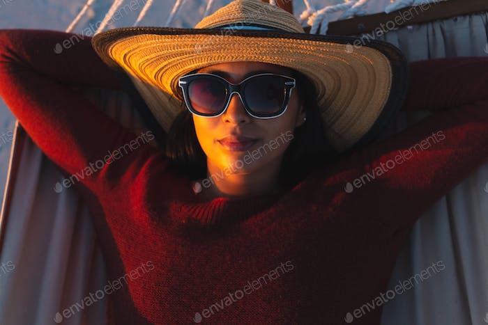 Retrato de mujer de raza mixta feliz en vacaciones en la playa mirando a la cámara acostado en la hamaca durante el atardecer