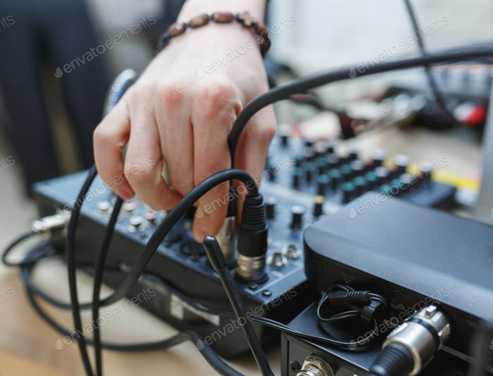 DJ connects the sound equipment for the event or party.