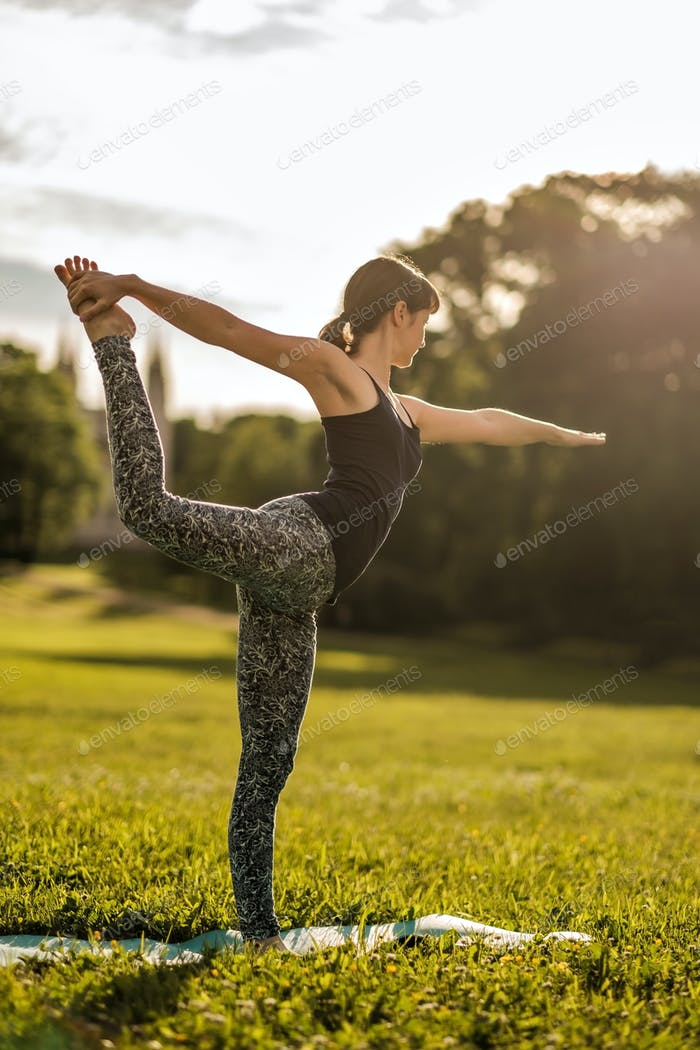 Young attractive woman doing dancers yoga pose outdoors on field