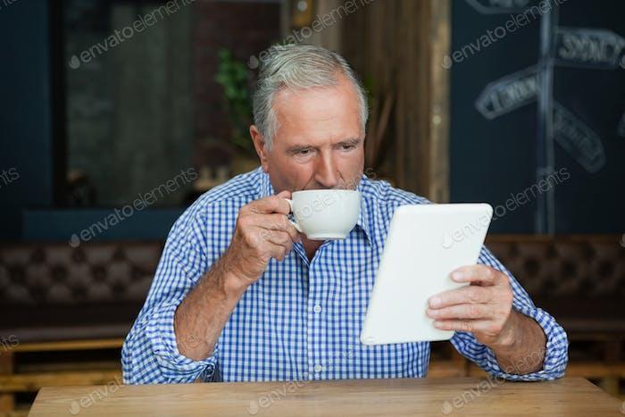 Senior Mann mit digitalen Tablette während Kaffee trinken