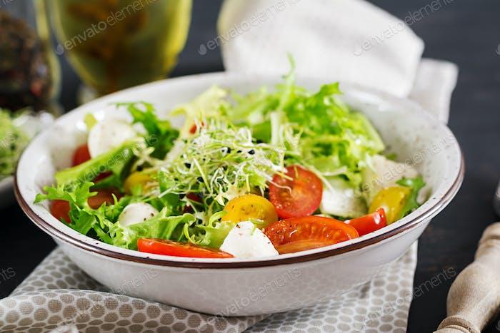 Vegetarian salad with cherry tomato, mozzarella and lettuce. Italian cuisine.