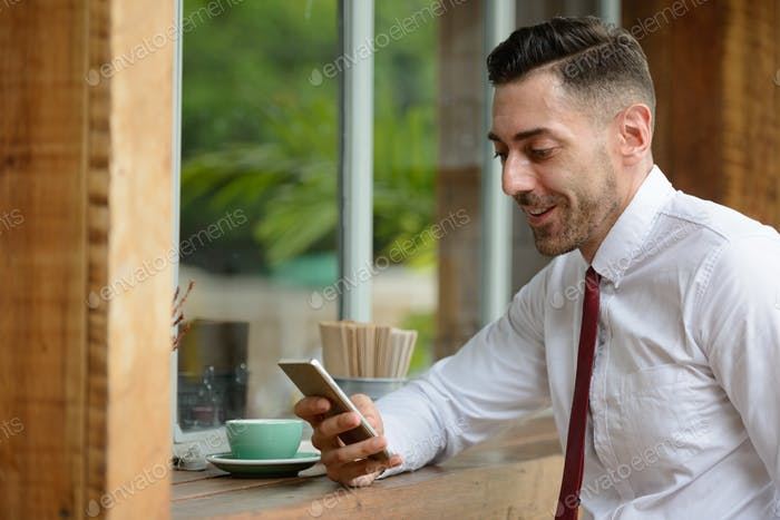 Profile view of happy handsome businessman using phone at the coffee shop