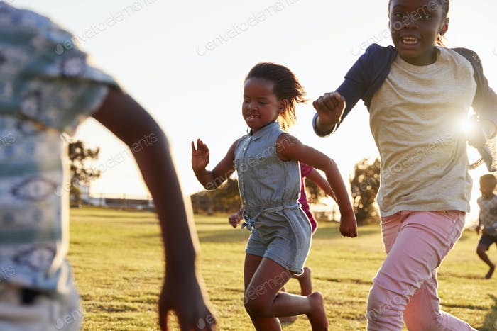 Elementary school kids running in an open field, close up