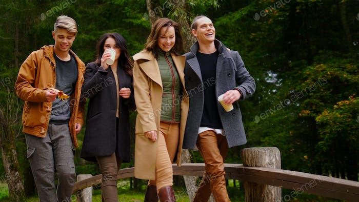 Друзья ходят по деревянному мосту в осеннем парке