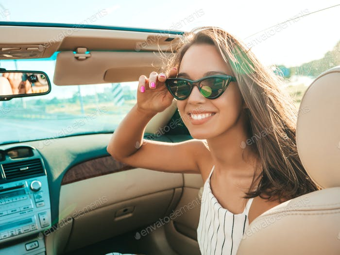 Portrait of young funny woman driving cabriolet car