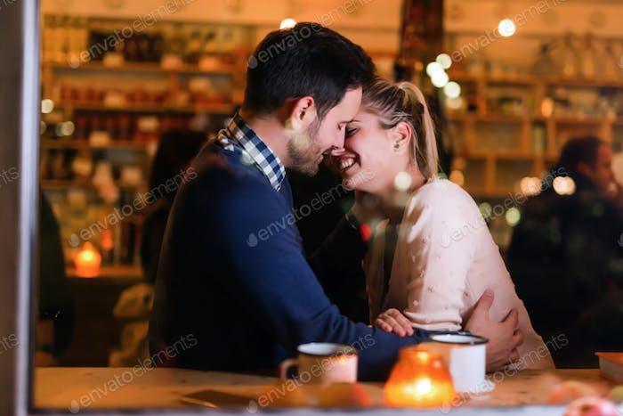 glücklich paar küssen in bar und mit date