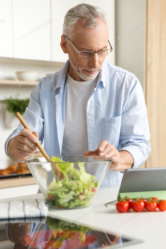 Handsome concentrated mature man cooking salad using tablet
