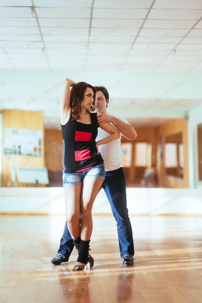 Beautiful couple of professional artists dancing passionate danc