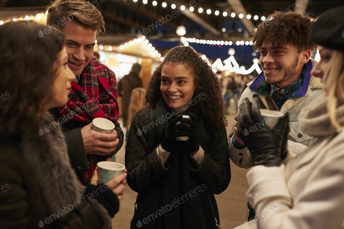 Group Of Friends Drinking Mulled Wine At Christmas Market